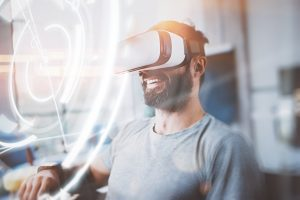 Concept of digital screen,connection and interfaces.Smiling hipster enjoyingvirtual reality glasses in modern design home studio.Smartphone use with VR goggles headset.Horizontal,flare,blurred